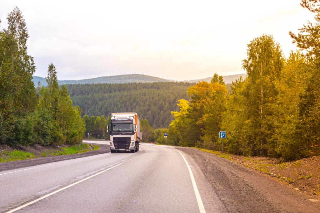 long-truck-drives-along-road-climbing-uphill-among-mountains-forests